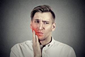 Closeup portrait young man with sensitive toothache crown problem about to cry from pain touching outside mouth with hand isolated on gray background. Negative human emotion face expression feeling