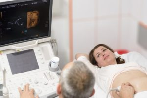 Doctor doing 3d ultrasound on belly of pregnant woman in clinic